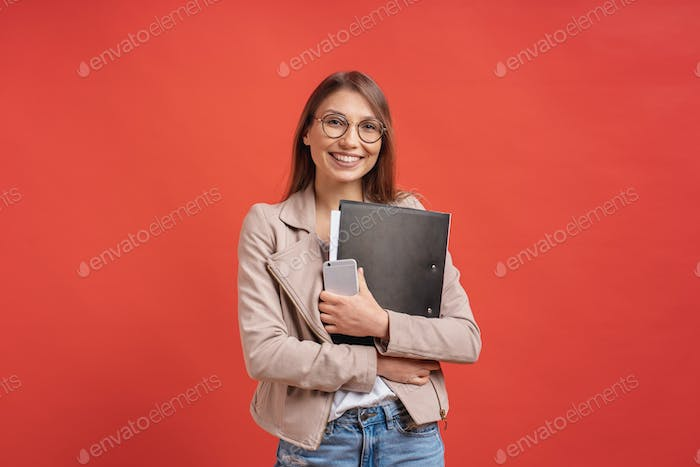 Young smiling student or intern in eyeglasses standing with a folder on red background.