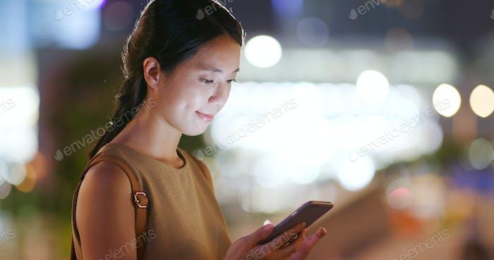 Frau Nutzung des Mobiltelefons mit Unschärfe Stadt am Abend