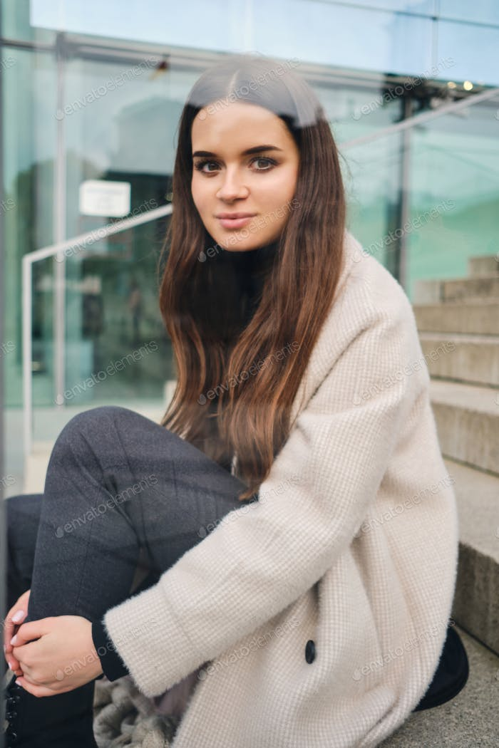 Pretty brunette girl in coat dreamily looking in camera sitting on strairs