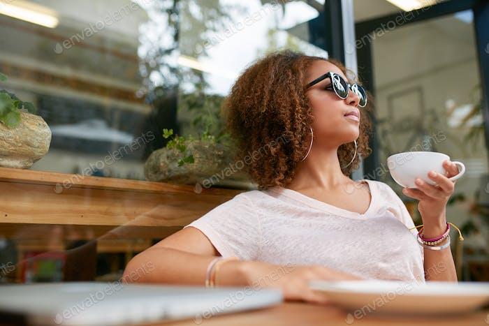 Stilvolle Mädchen mit Kaffee am Bürgersteig Café