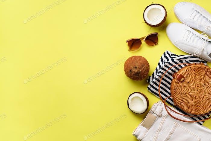 Weibliche weiße Turnschuhe, Jeans, gestreiftes T-Shirt, Rattan-Tasche, Kokosnuss und Sonnenbrille auf gelb