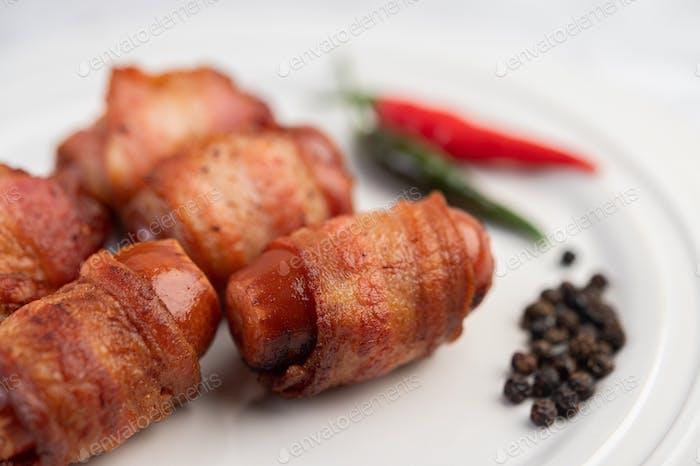 Wurst gewickelter Schweinebauch auf einem weißen Teller.