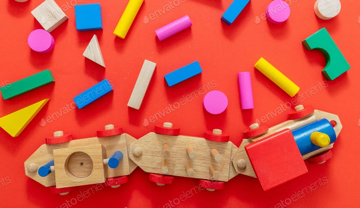 Juguete de tren y bloques de colores de madera sobre fondo de color rojo