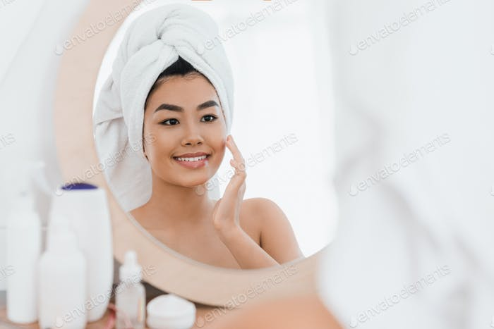 Cheerful asian young woman applying beauty product