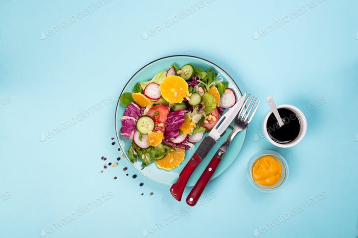 Fresh vegetables salad with various dressing on blue background, top view, border.