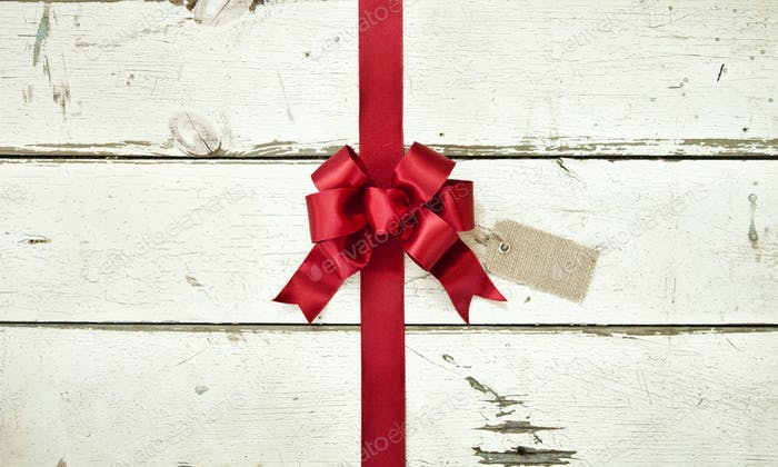 Red Christmas Bow on Old White Wood Background