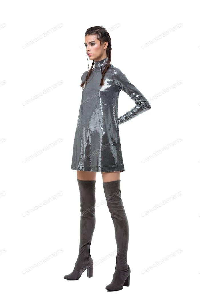 Junge hübsche Dame stehend im Kleid in Pailletten und kniehohe Stiefel auf weißem Hintergrund