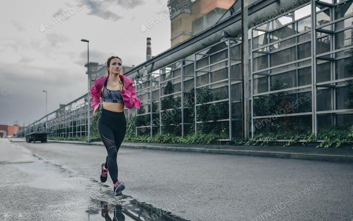 Sportlerin läuft in einer Industriezone