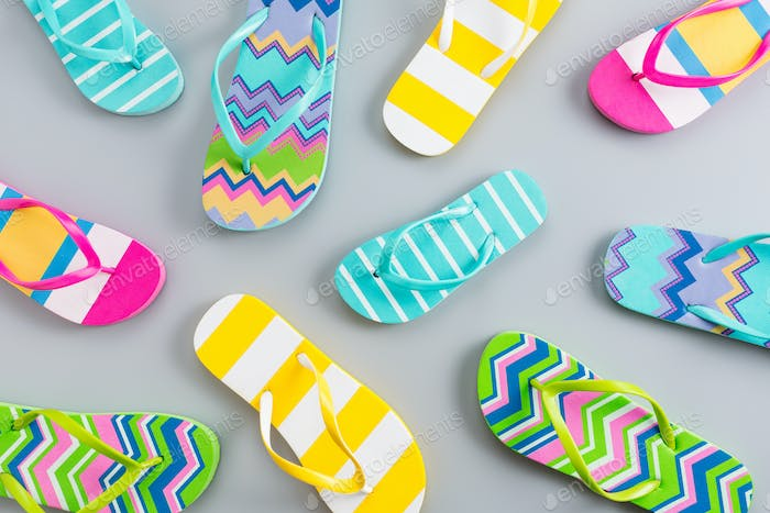 Colorful flip flops on grey background