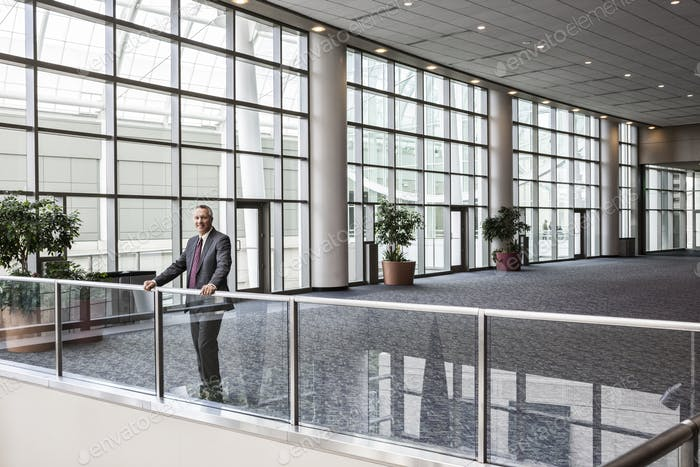 Caucasian businessman waiting for an appointment standing in a large open lobby area.