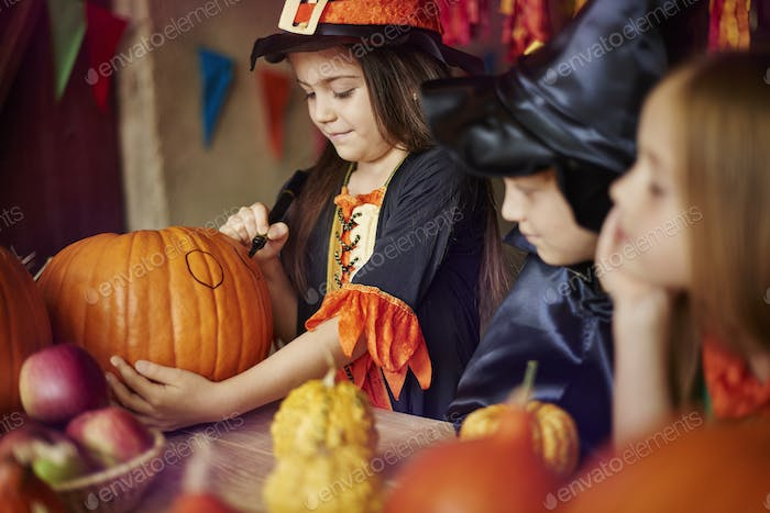 Group of children decorating Halloween pumpkins