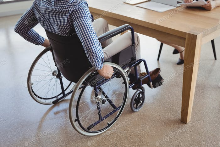 Handicapped executive sitting on wheelchair at desk