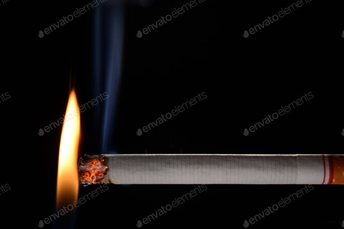 Cigarette being lit by small flame on black background