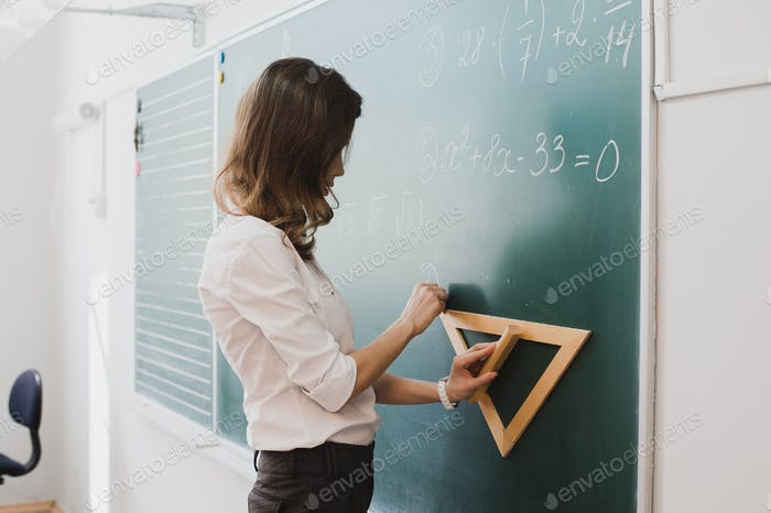 Smart student or teacher drawing mathematic formula at blackboard, dressed in university uniform