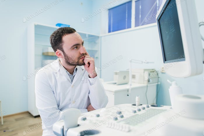 Portrait of a thinking doctor near sceen of medical equipment.