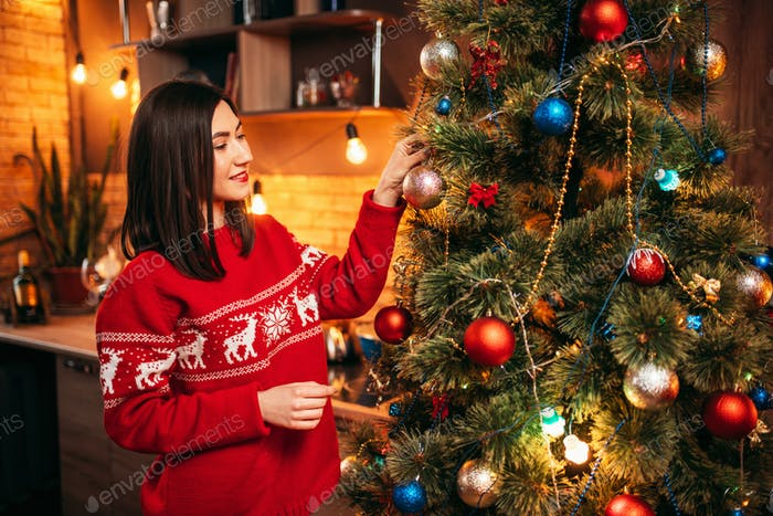 Young woman in red sweater decorate christmas tree