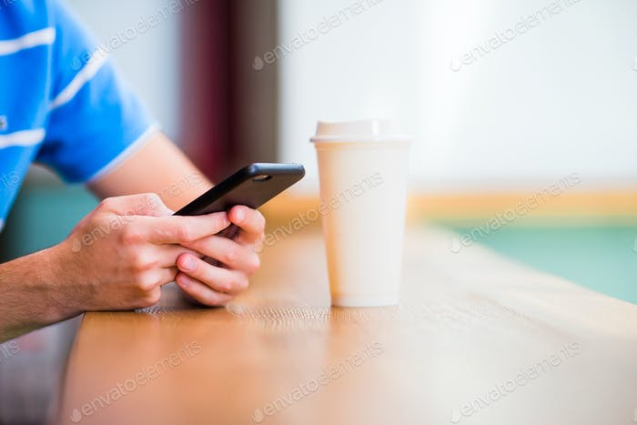 Closeup of male hands holding cellphone and class of cofee in cafe. Man using mobile smartphone