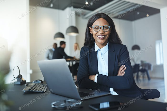 Smiling African American businesswoman sitting at her office desk