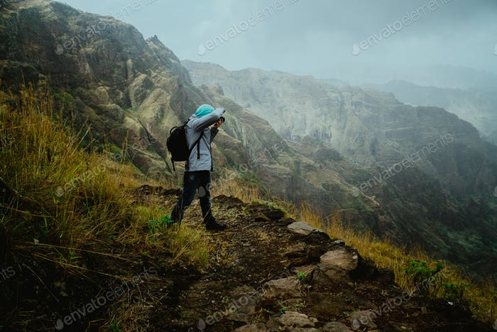 Hiker with camera in the steep mountainous terrain shooting a foto of lush canyon valley on the path