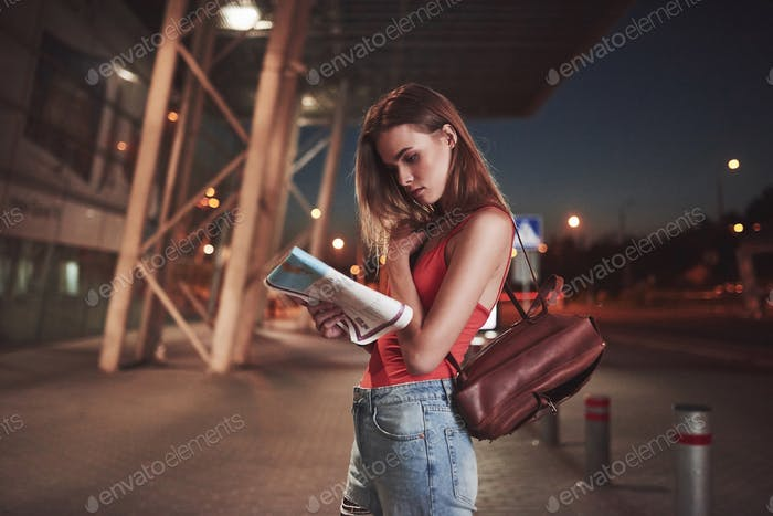 Young girl costs at night near the terminal of the airport or station and reading city map