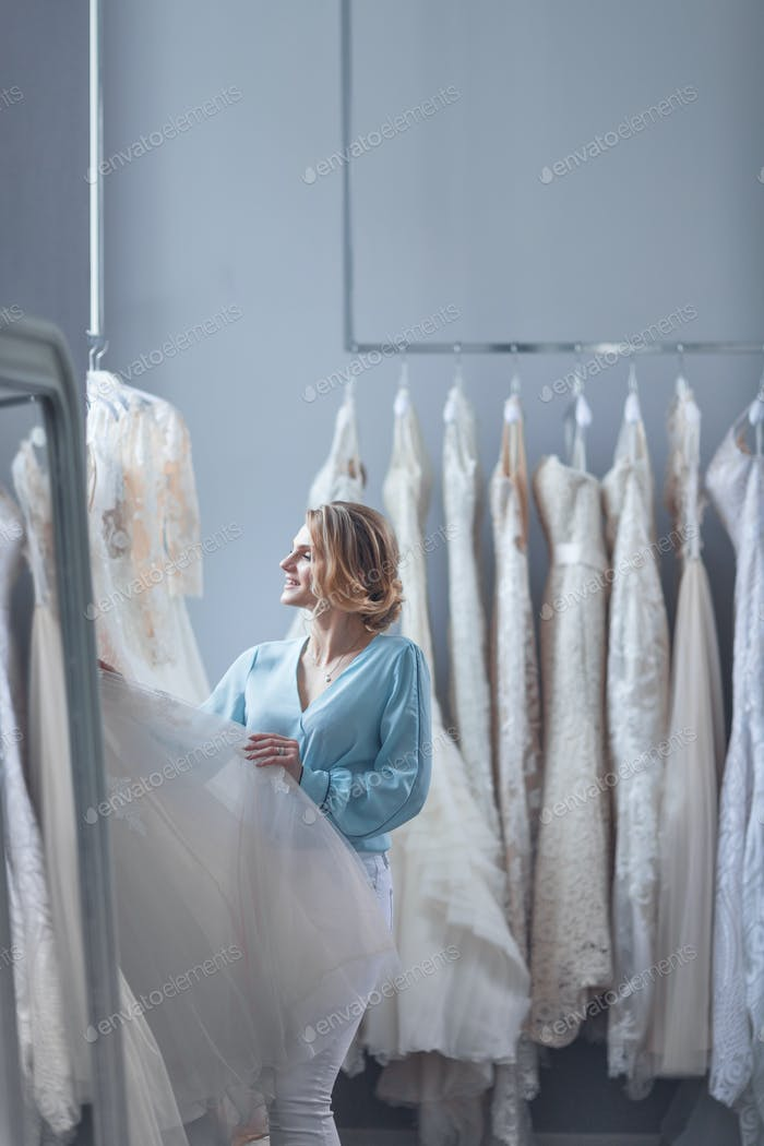 Young customer chooses a wedding dress in the store