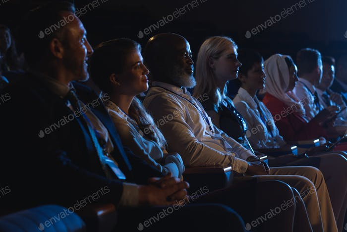 Side view of mixed race business colleagues sitting and watching presentation with audience