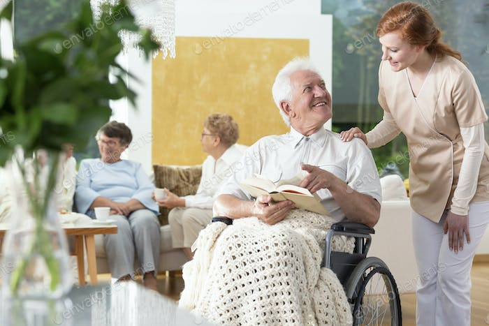 Happy paralyzed senior man in a wheelchair reading a book and a