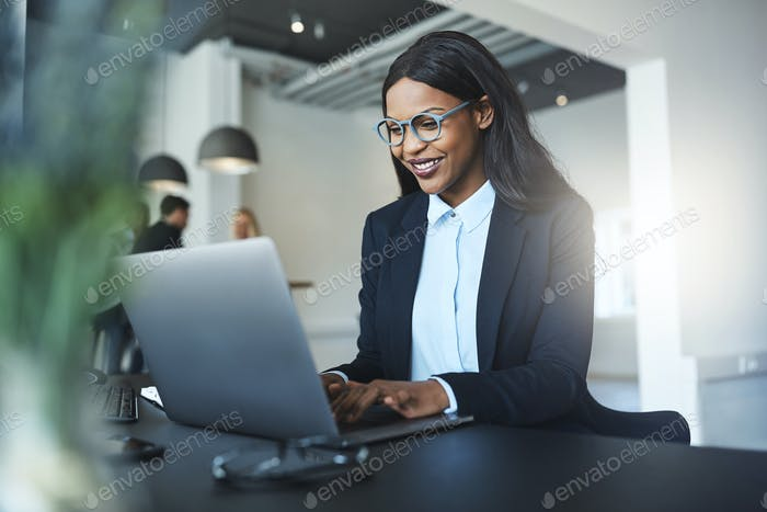 Smiling African American businesswoman using a laptop at her desk