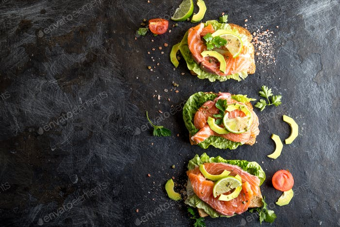 Open salmon sandwiches with avocado. Black background. Copy space.