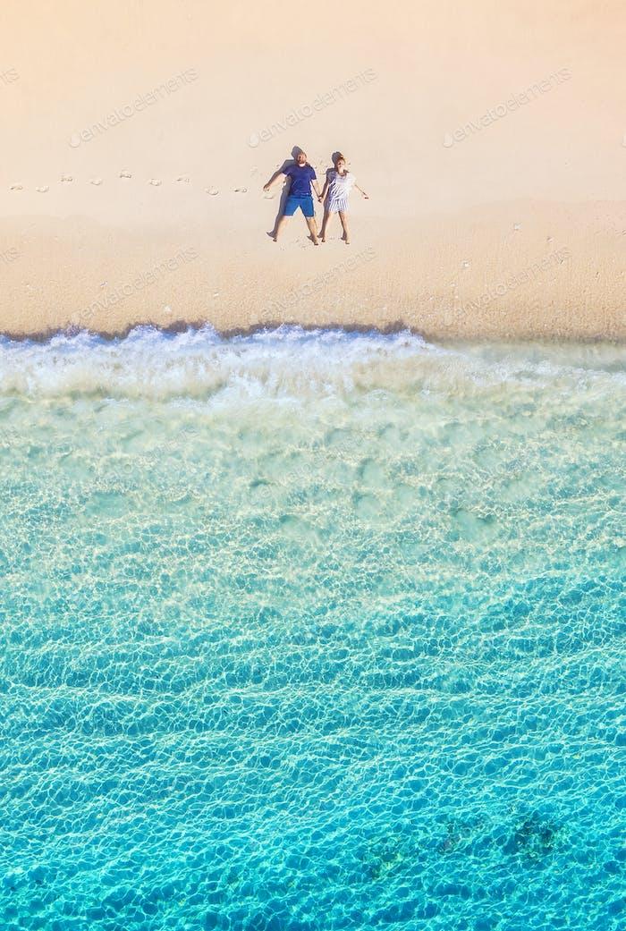 Ein paar Leute ruhen sich am Strand aus. Der Blick aus der Luft. Insel Bali, Indonesien.