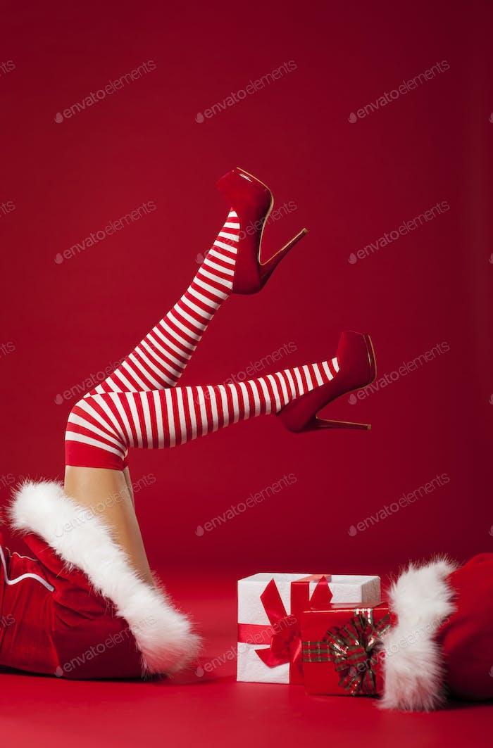 Mrs Santa Claus Beine in gestreiften Strümpfen mit Weihnachtsgeschenken