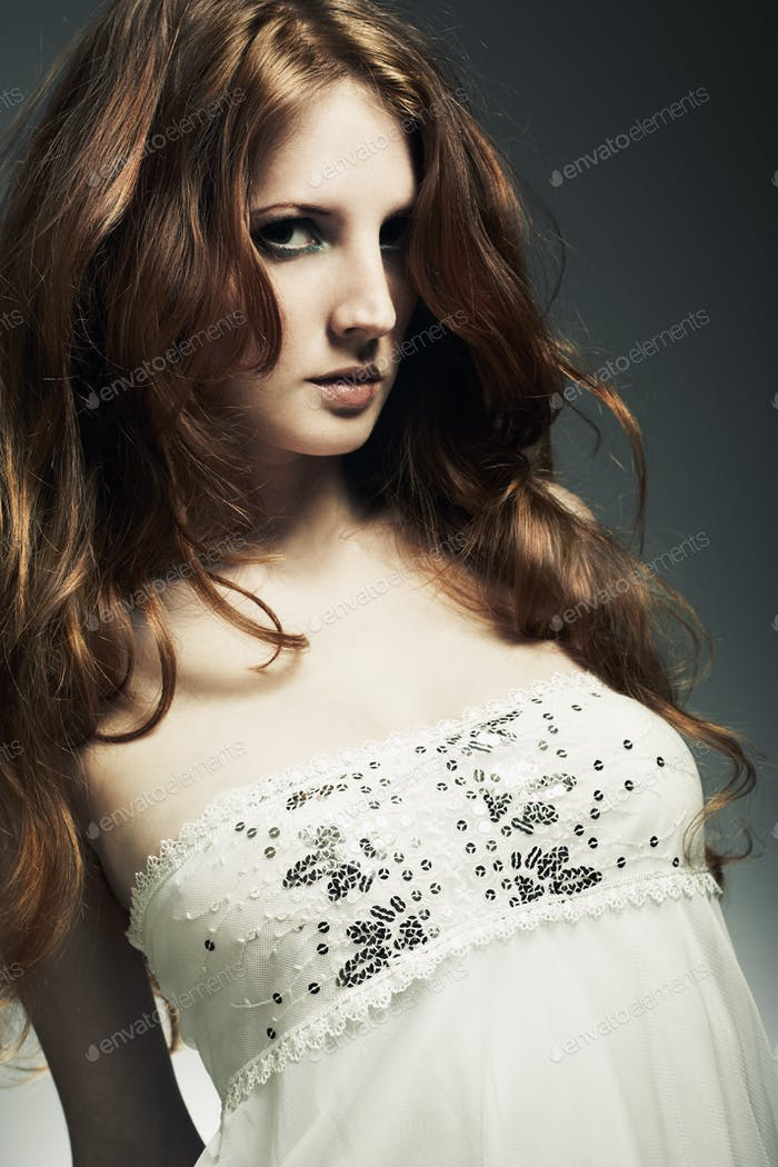 Fashion portrait of a young beautiful redheaded woman