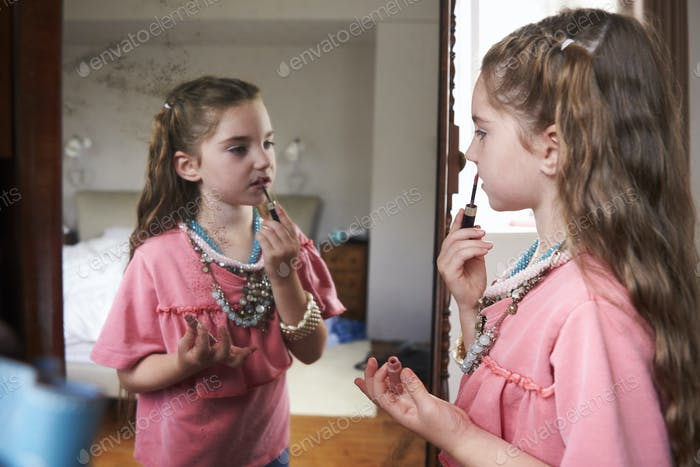 Young Girl Playing Dressing Up Game In Front Of Mirror At Home