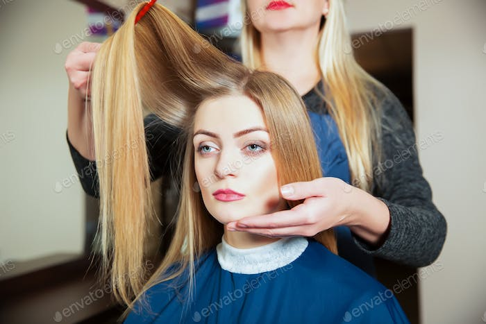 Hairdresser making hairstyle with hairbrush.