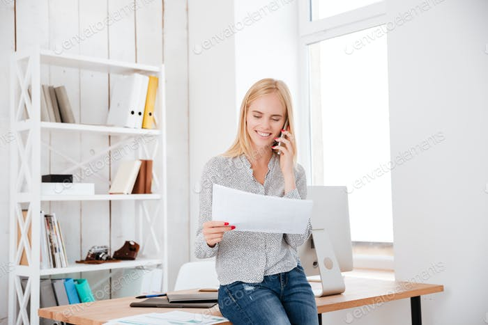 Smiling happy woman talking on mobile phone and holding document