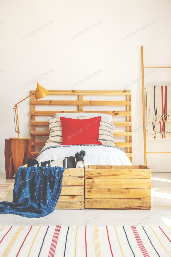 Vertical view of comfortable bed with wooden headboard, red pill