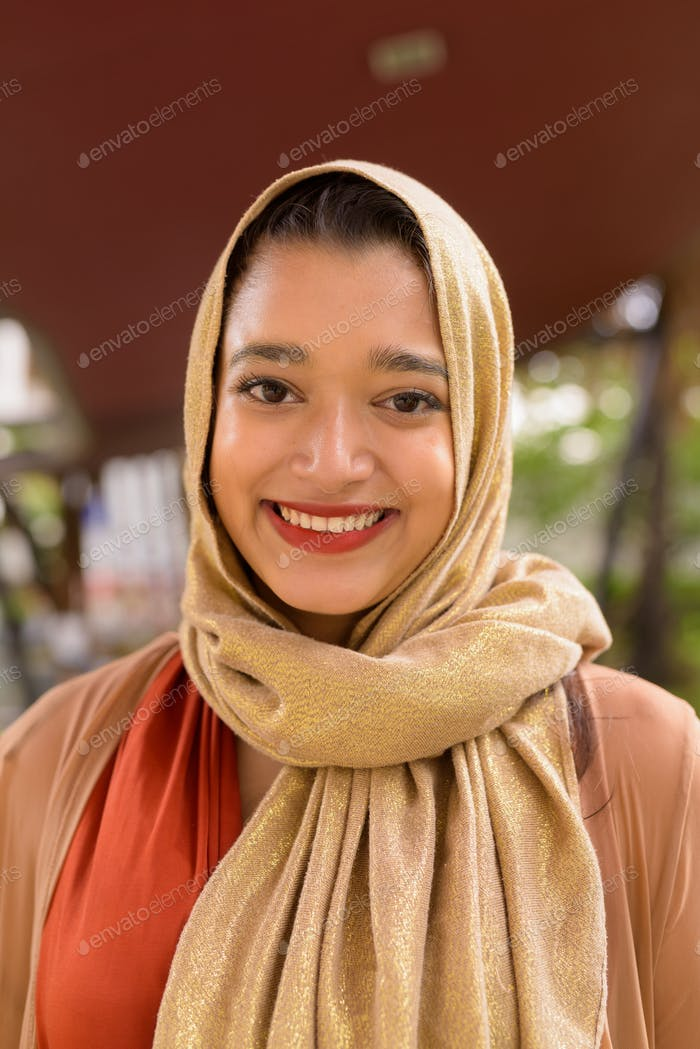 Face of happy young beautiful Indian Muslim woman smiling in the city with nature