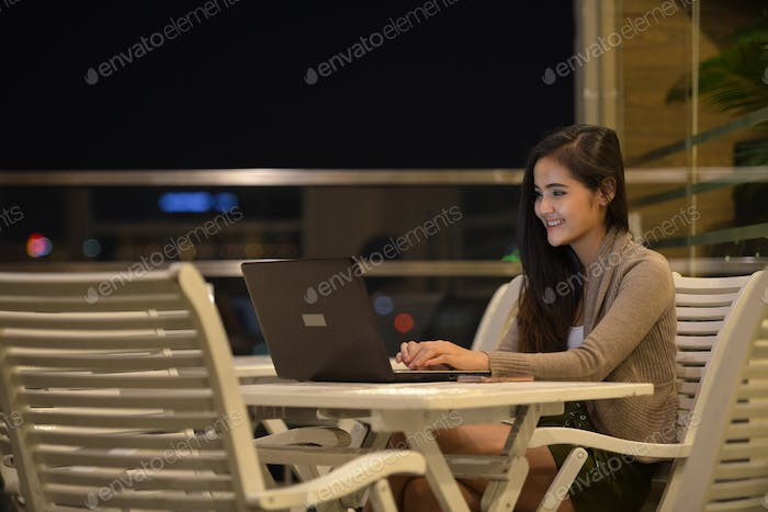Happy Woman Using Laptop Computer Outdoors At Night
