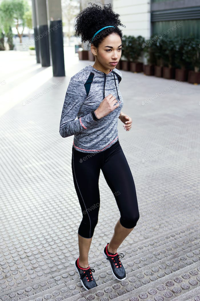Beautiful young woman running in urban environment.