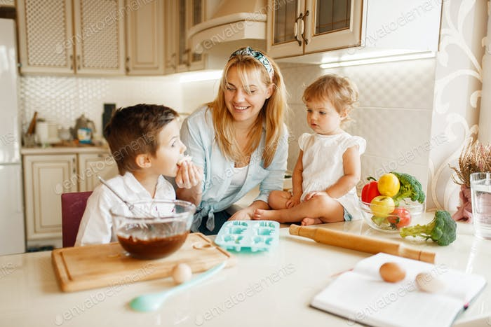 Mother and her kids tastes melted chocolate