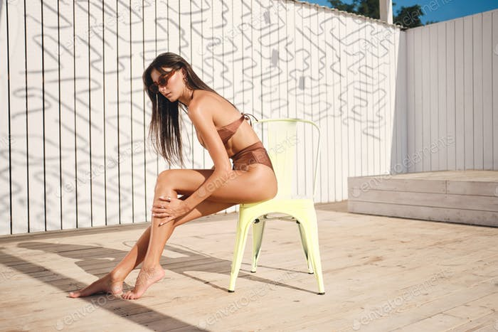 Beautiful sexy brunette girl smearing body with sunscreen cream sunbathing on chair on beach