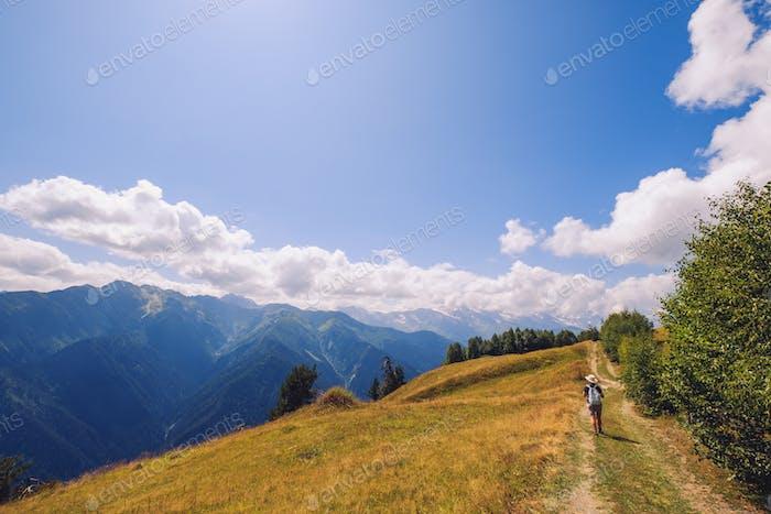 Mujer senderismo en las montañas y prados del Parque nacional de Svaneti, Georgia