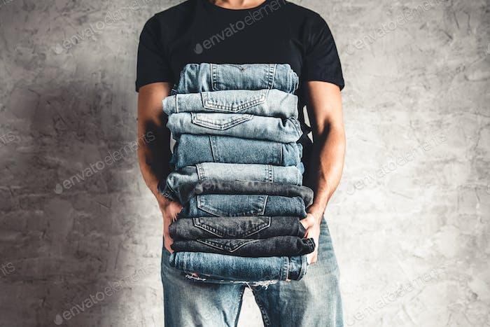 Nahaufnahme Stapel von gefalteten Denim Blue Jeans in der Hand über grauen Wandhintergrund, Kopierraum