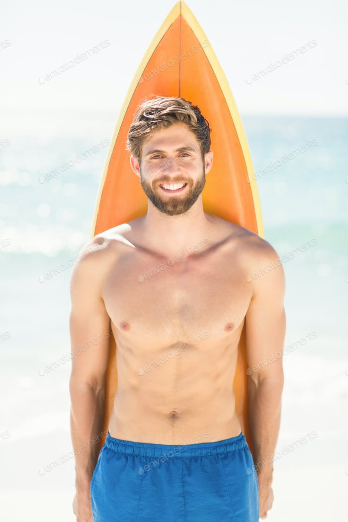 Handsome man holding surfboard at the beach