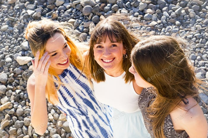 three young women hug themselves in a sunny day.