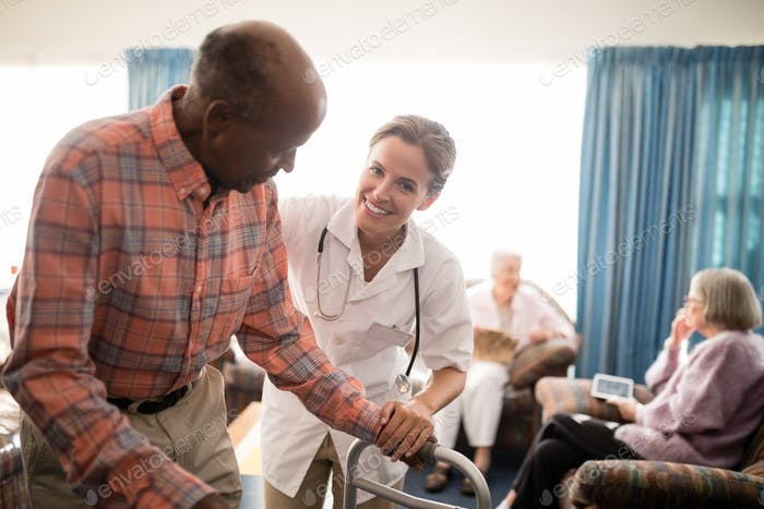 Portrait of smiling female doctor with senior man standing by walker against window