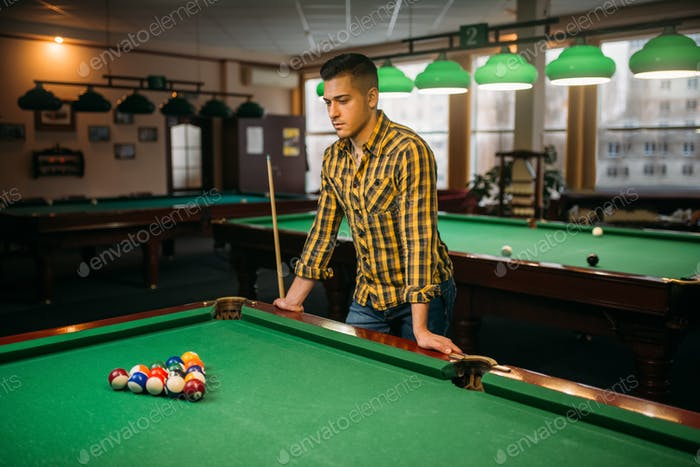 Male billiard player, poolroom on background