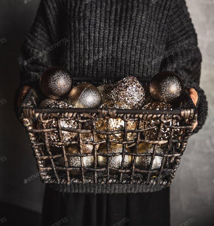 Drahtkorb voller Weihnachts- oder Neujahrsbaum goldene Vintage-Dekoration Spielzeug in den Händen der Dame
