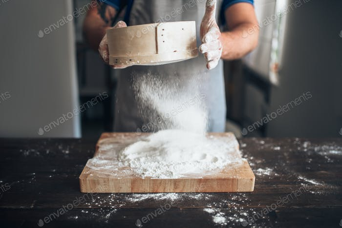 Male baker hands filters the flour through a sieve