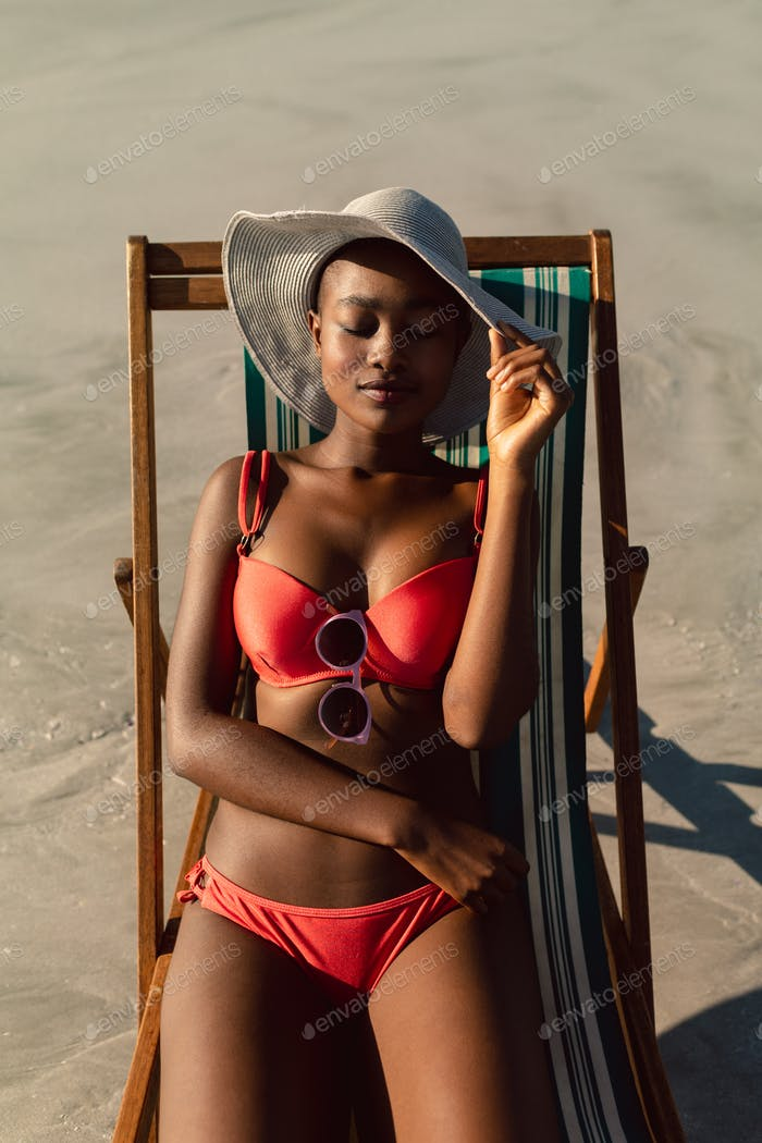 Front view of young African-american woman sleeping in a beach chair on the beach